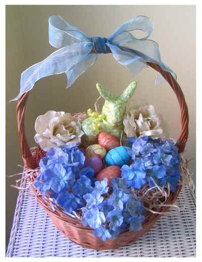 Easter basket with decorated eggs, flowers and bunny.