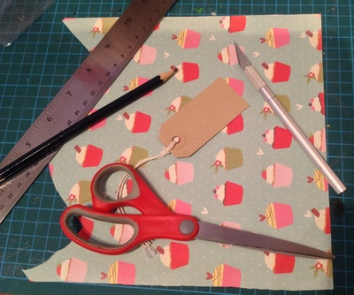 Gift wrap, gift tags, scissors, craft knife, ruler, cutting board