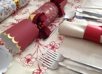 Natural tablecloth, hessian napkin, red berry runner, red cracker, ribbon napkin tie